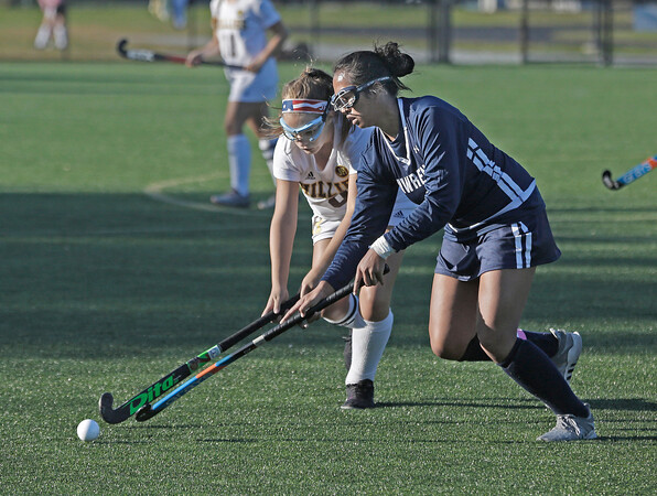 MIKE SPRINGER/Staff photo<br /> Haverhill's Catie Chadwick, left, competes for the ball with Duongdara Kim of Lawrence during varsity field hockey play at Haverhill<br /> 9/18/2019