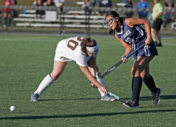 MIKE SPRINGER/Staff photo<br /> Lawrence's Jadelyn Him, right, hits the ball past Sydney Keyes of Haverhill during varsity field hockey play Wednesday in Haverhill.<br /> 9/18/2019