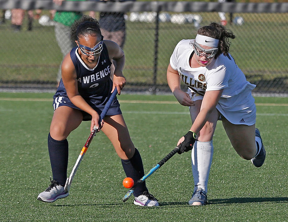 MIKE SPRINGER/Staff photo<br /> Haverhill's Sydney Keyes, right, knocks the ball away from Shanalee Then of Lawrence during varsity field hockey play at Haverhill<br /> 9/18/2019