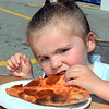 CARL RUSSO/Staff photo. Brynna Wasmer, 3 of Haverhill uses one hand to eat her pepperoni pizza. Team Haverhill's River Ruckus 2019 was held Saturday in downtown Haverhill on Washington Street. 9/21/2019