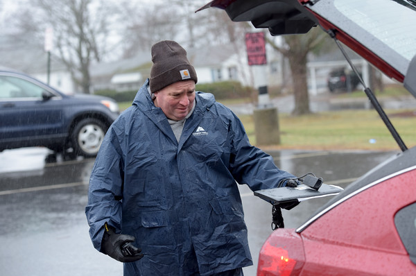 TIM JEAN/Staff photo  <br /> <br /> Consentino Middle School Principal John Mele places a chromebook computer into the back of a parents vehicle outside the school in Haverhill. Hundreds of parents picked up the computers so students can continue learning from home during the COVID-19 pandemic.    4/3/20