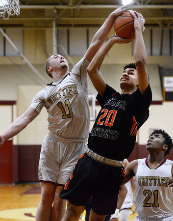 CARL RUSSO/Staff photo Whittier's Anthony Couture blocks the attempted lay up by Greater Lawrence's Antonio Valenzuela. Greater Lawrence Tech. defeated Whittier Tech. 53-42 in boys' basketball action. 2/03/2020