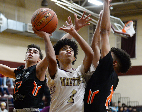 CARL RUSSO/Staff photo Whittier's Angel Rodriguez drives to the hoop against Greater Lawrence's defenders. Greater Lawrence Tech. defeated Whittier Tech. 53-42 in boys' basketball action. 2/03/2020