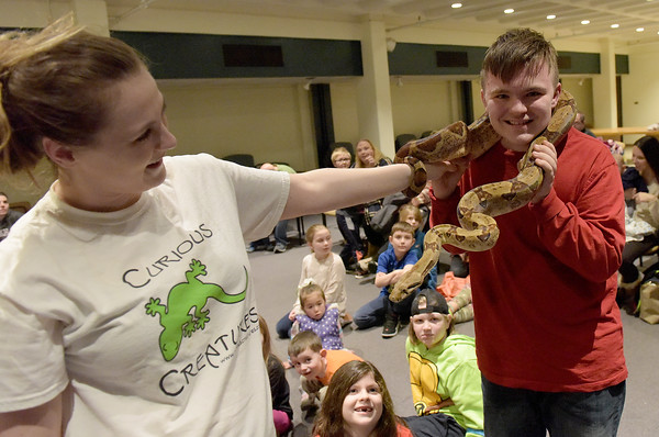 TIM JEAN/Staff photo <br /> <br /> Danny Ovalle, 15, right, has a long boa constrictor snake placed around him held by Chelsea Holt of Curious Creatures, during a live animal program at the Haverhill Public Library.   1/3/20