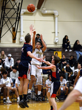 CARL RUSSO/Staff photo. Haverhill's Elijah Haas takes the long three point jump shot over Central defenders. Central Catholic defeated Haverhill 48-39 in boys basketball action Friday night. 1/10/2020
