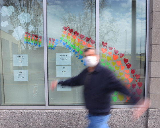 CARL RUSSO/Staff photo. A man strolls pass the front window of Harbor Place Residences decorated with hearts. The building is located at 44 Merrimack Street. Several downtown Haverhill businesses are displaying messages of hope in their store windows during the coronavirus crisis. 5/06/2020