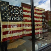 CARL RUSSO/Staff photo. Battle Grounds Coffee on Washington Street displays a message on their window with the American flag as the backdrop. Several downtown Haverhill businesses are displaying messages of hope in their store windows during the coronavirus crisis. 5/06/2020