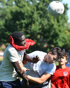 CARL RUSSO/Staff photo Seniors Christian Mugisha, left and Muhammedeid Shquair collide as they both go up to head the ball during a practice scrimmage.    The Haverhill high boys soccer teams (varsity and JV) held their first Saturday morning soccer practice on the new high school field. 8/24/2019