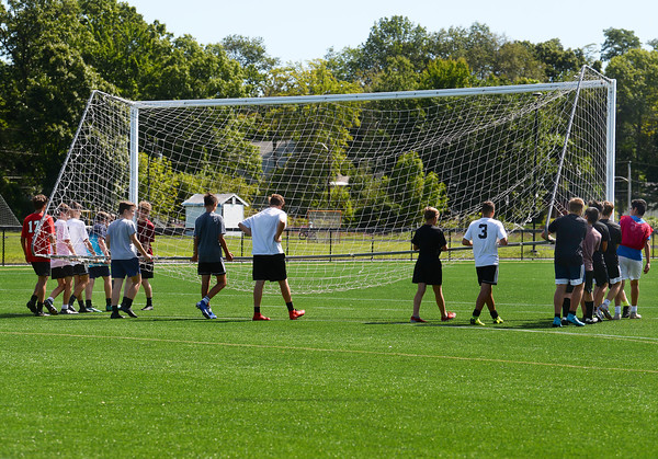 CARL RUSSO/Staff photo The Hillies work together to move one of the soccer nets.   The Haverhill high boys soccer teams (varsity and JV) held their first Saturday morning soccer practice on the new high school field. 8/24/2019