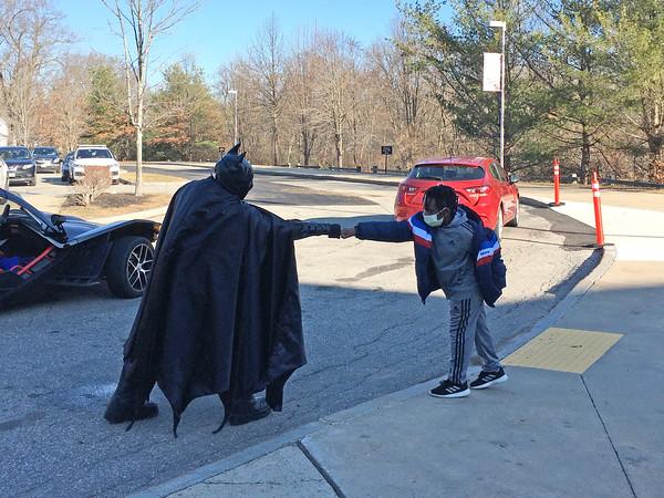 ALLISON CORNEAU/Staff photo<br /> Batman greets a young fan with a COVID-friendly fist bump at Bradford Elementary School.