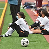 CARL RUSSO/staff photo Greater Lawrence's Lisette Perez, left and Emily Then, right, and other girls playing on the boys team watch the action while waiting to play. Whittier Tech. high school defeated Greater Lawrence Tech. 7-0 in boys'  soccer action Wednesday afternoon. 3/24/2021