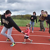 CARL RUSSO/staff photo Haverhill high senior track member, Megan McAuliffe is handed the baton by Tony Sapienza's great grandson Brennan Jenkins, 2, during a ceremonial run around the track. He is the son of Melissa Donais, Tony's granddaughter and Nate Jenkins of North Andover. Tony's grandchildren and great grandchildren participated in the ceremonial run. Seen here are grandchildren Jenn Donais, right of Haverhill; Ksenia Kessler and her brother David, both of Andover.  <br /> <br /> The dedication of the renovated Tony Sapienza Memorial Track and Field at Haverhill High was held Wednesday, May 12. Honored guests,  included various city officials and guest speakers Mayor James Fiorentini and Tom Derderian, a noted runner and author. <br /> <br /> Tony Sapienza's family; his daughters Toni Sapienza-Donais of Haverhill and Joy Sapienza-Kessler of North Andover and Tony's grandchildren, Melissa Donais and her husband Nate Jenkins, Jenn Donais and Chris Donais, David Kessler and Ksenia Kessler, and great grandchildren Brennan, 2 and Audrey Jenkins, who celebrated her first birthday on the day of the dedication.<br /> <br />  During the ceremony, Haverhill high senior track team members, Ariann LeCours and Aidan Corcoran were each awarded $500 scholarships, courtesy of the Sapienza/Donais family and Dick and Rose Mary Early of Early Construction Inc. 5/12/2021