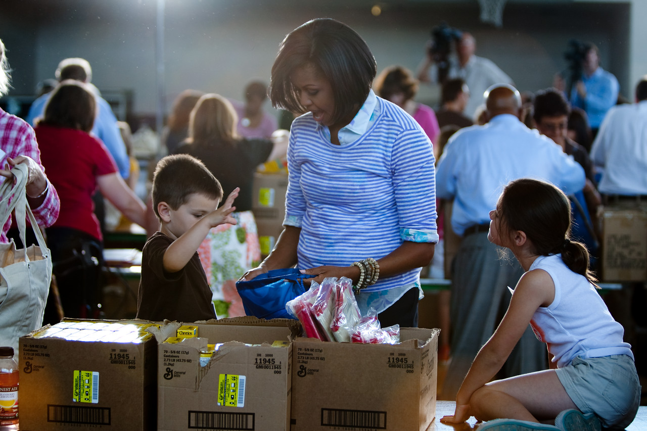 First Lady Michelle Obama helps two children fill care packages designed to encourage children to lead healthy summers at the launch of Let's Read. Let's Move. on June 8, 2010.