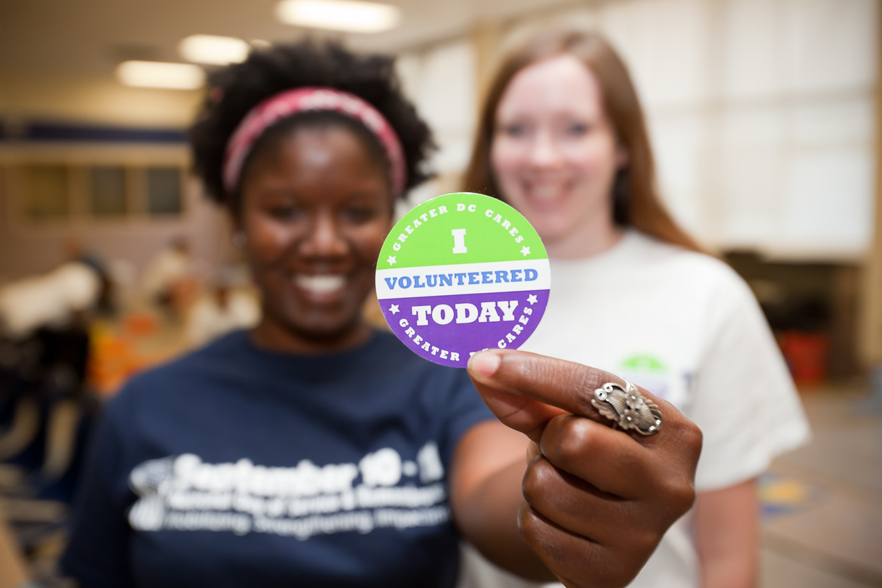 A volunteer holds a sticker commemorating service on the 2010 September 11th National Day of Service and Remembrance at Ron Brown Middle School in Washington, DC.