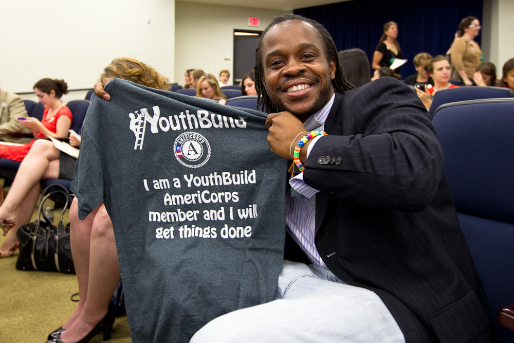 An AmeriCorps Alum shows of his AmeriCorps YouthBuild shirt. Corporation for National and Community Service Photo.