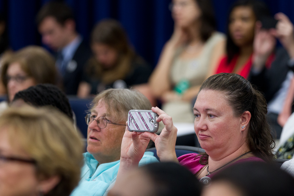 An AmeirCorps Alum takes a photo of a speaker at the AmeriCorps Alums Day at the White House. Corporation for National and Community Service Photo