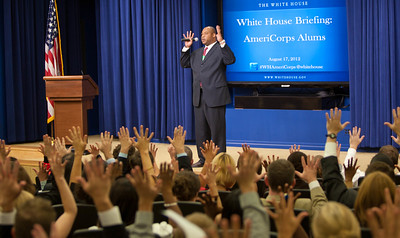 A White House offical gets the audience to stretch after serveral hours of speakers on AmeirCorps and national service. Corporation for National and Community Service Photo.