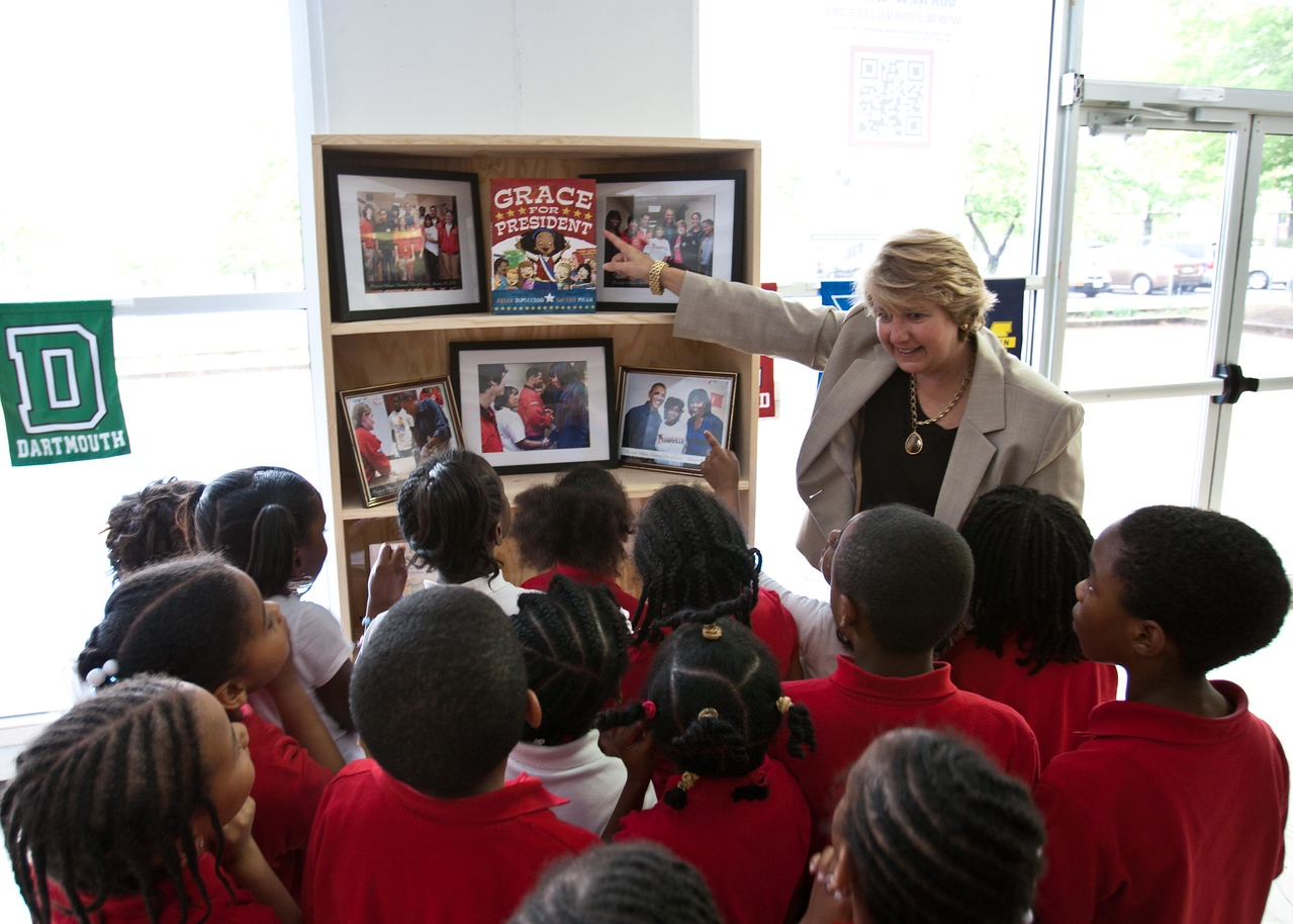 Corporation for National and Community Service, CEO Wendy Spencer shows students the book she has chosen to add to the shelf on display in the schools main entrance. Corporation for National and Community Service Photo.