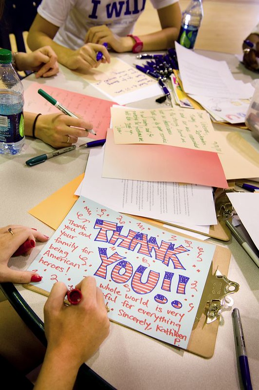 A volunteer writes a thank you letter to the troops at a September 11th National Day of Service and Remembrance event organized by HandsOn Greater DC Cares and U.S. Vets -- United States Veterans Initiative. The event was attended by over 200 White House and Corporation for National and Community Staff and their families. (Corporation photo by Sam Kittner, 2011)