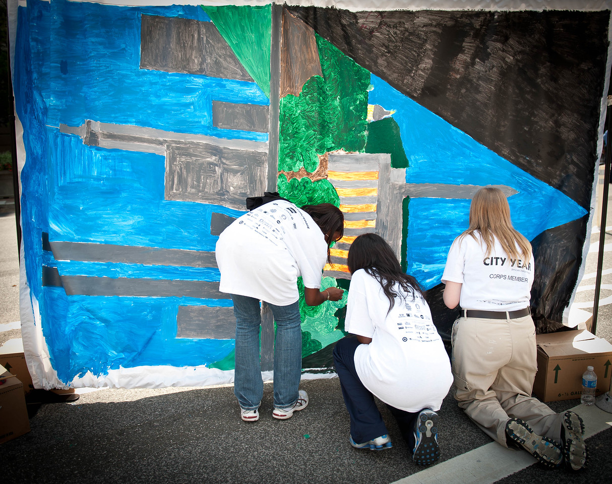 An AmeriCorps member with CityYear works with young volunteers to paint a portable mural at a September 11th National Day of Service and Remembrance event. The event was organized by Serve DC and Greater DC Cares as a Tribute to Service: Honoring the Victims, Survivors, and Heroes of 9/11. (Corporation photo by Steven E. Purcell, 2011)