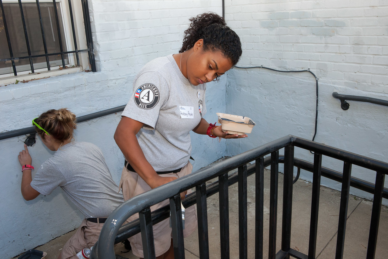AmeriCorps members painting railings in an apartment complex in Washington, D.C. Corporation for National and Community Service Photo.