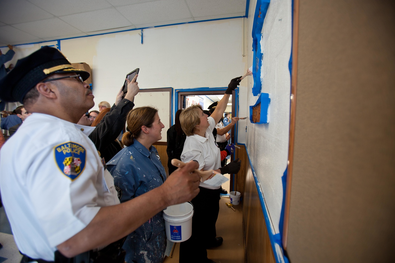 CNCS CEO Wendy Spencer paints alongside a police officer and AmeriCorps volunteers at a West Baltimore Police precinct at the Service Bowl in Baltimore, MD. Corporation for National and Community Service Photo.