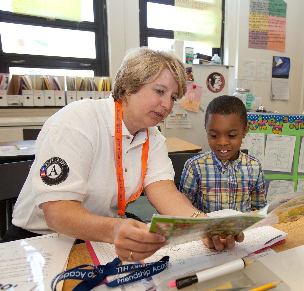 CNCS CEO Wendy Spencer reads to a young student at the Service Bowl in Baltimore, MD. Corporation for National and Community Service Photo.