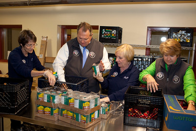 Senior Corps members, Mayor Scott Smith of Mesa, Ariz., and CEO, CNCS, Wendy Spencer pack food containers at the Pike Place Food Bank in Seattle, WA. Corporation for National and Community Service Photo.