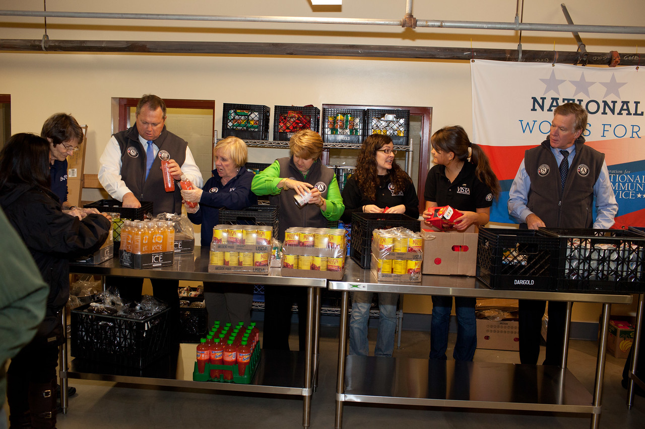 Senior Corps members, AmeriCorps VISTA members, AmeriCorps members serve with Mayor Christopher B. Coleman, of St. Paul, Minn., Mayor Scott Smith of Mesa, Ariz., and CEO, CNCS, Wendy Spencer pack food containers at the Pike Place Food Bank in Seattle, WA. Corporation for National and Community Service Photo.