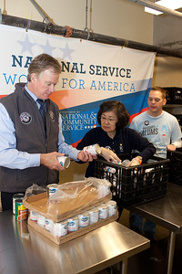 Seniors Corps member, and an AmeriCorps alum member serve alongside Mayor Christopher B. Coleman, of St. Paul, Minn. with packing food containers at Pike Place Food Bank in Seattle, WA. Corporation for National and Community Service Photo.