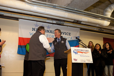 Mayor Christopher B. Coleman, of St. Paul, Minn. welcomes Mayor Scott Smith of Mesa, Ariz. to speak at Pike Place Food Bank in Seattle, WA for the launch of Mayors Day of Recognition for National Service. Corporation for National and Community Service Photo.