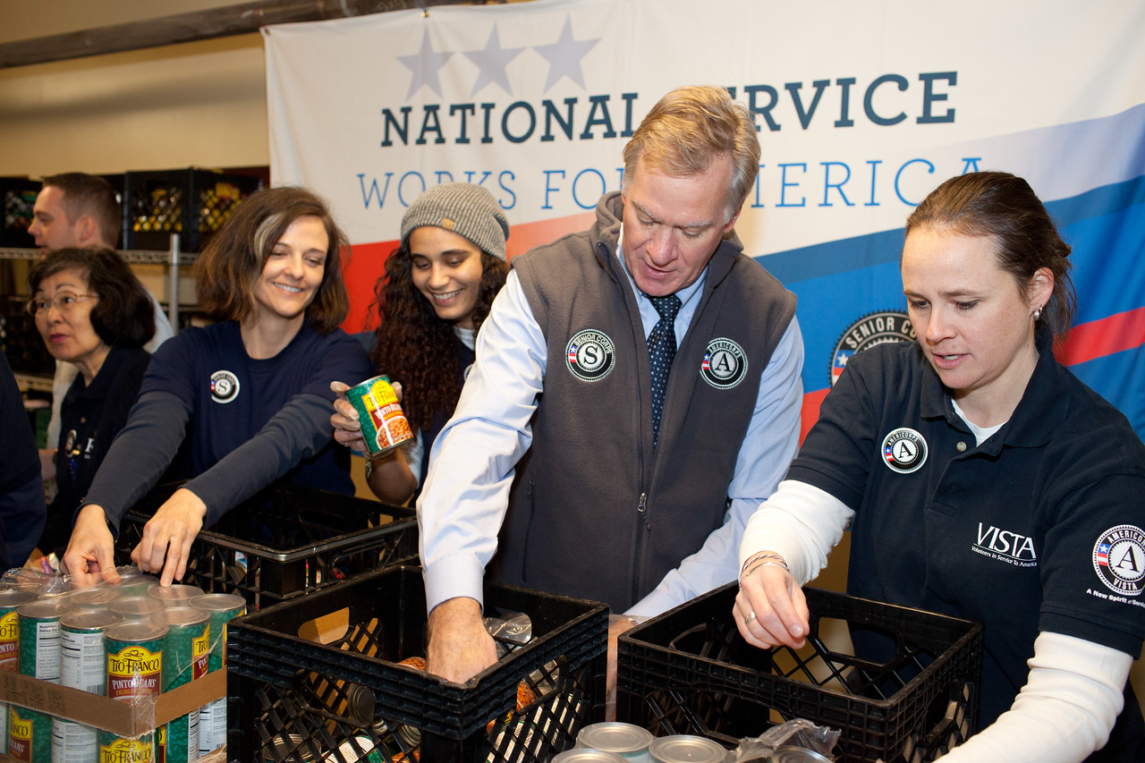 Seniors Corps member, and AmeriCorps VISTA members serve alongside Mayor Christopher B. Coleman, of St. Paul, Minn. with packing food containers at Pike Place Food Bank in Seattle, WA. Corporation for National and Community Service Photo.