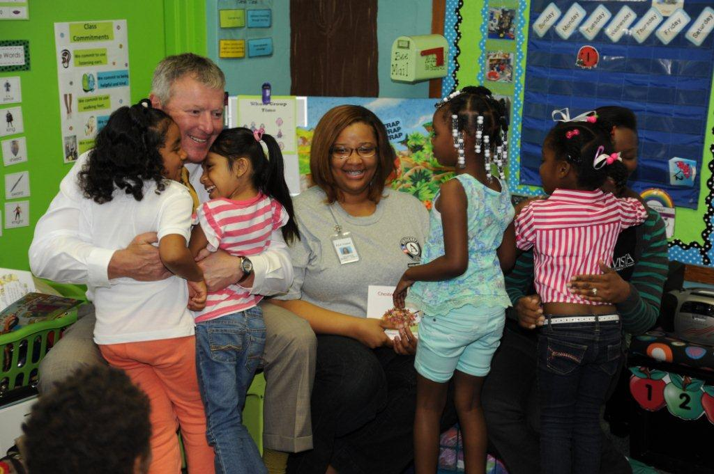 Mayor Buddy Dyer (Orlando, FL) hugs young service recipients alongside an AmeriCorps member during the Mayors Day of Recognition for National Service on April 1, 2014. Corporation for National and Community Service Photo.