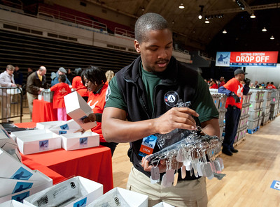 An AmeriCorps member prepares items to pack in kits for overseas troops at the DC Armory during 2013 National Day of Service and MLK Day activities. (Corporation for National and Community Service photo)
