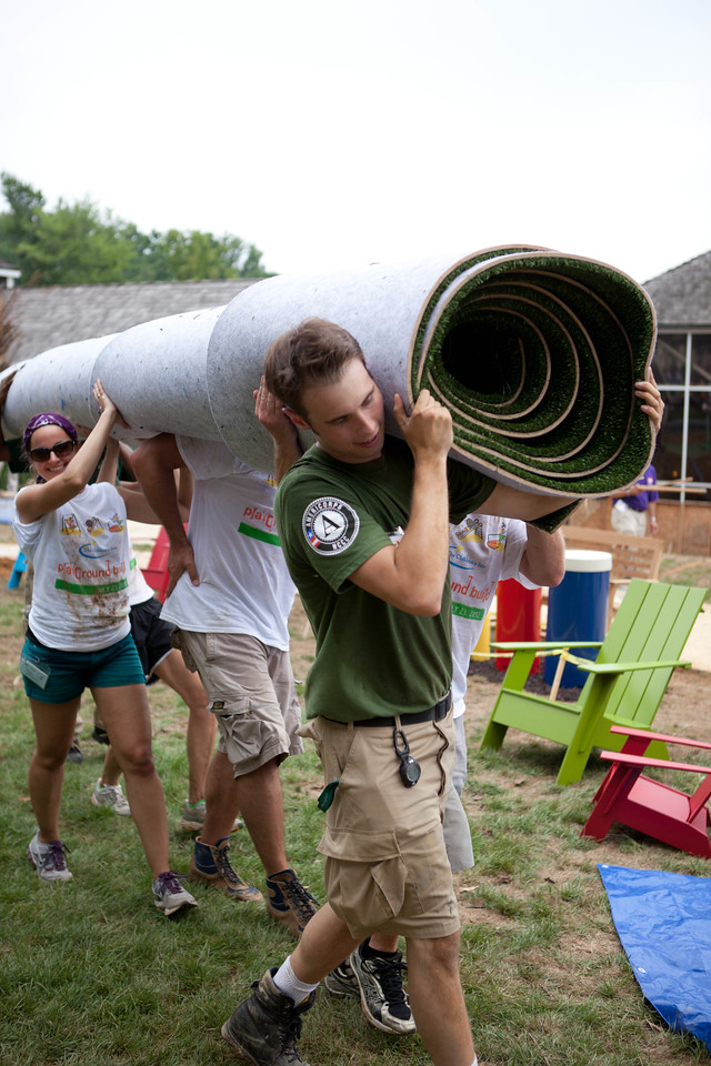 Volunteers and NCCC member, Tristan carry turf at the KaBOOM! build at NIH. Corporation for National and Community Service Photo