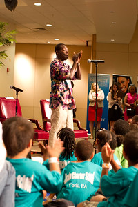 Wolf Trap Teaching Artist Kofi Dennis getting children warmed up at Let's Read Let's Move July 2012. Corporation for National and Community Service Photo.