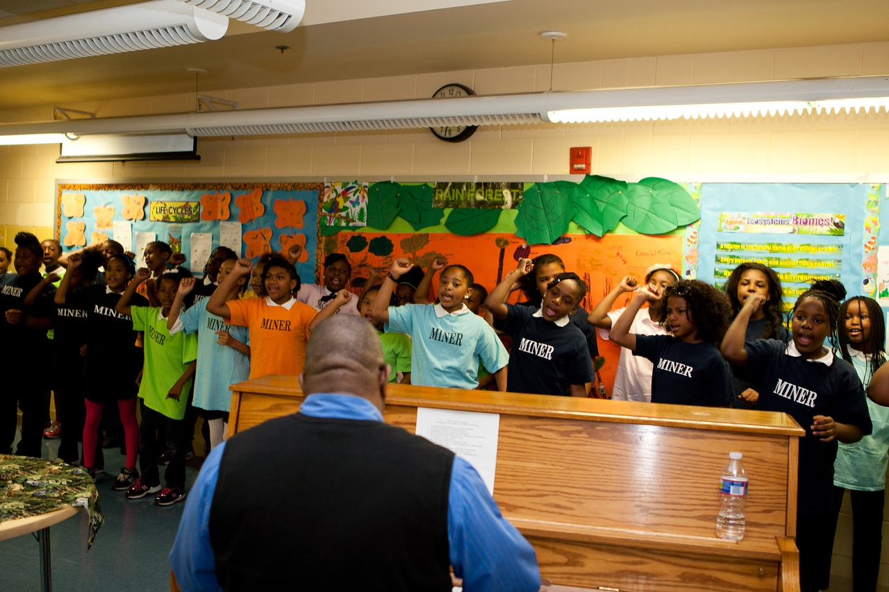 The Music Director at Miner Elementary and students welcome visitors with song. Corporation for National and Community Service Photo.