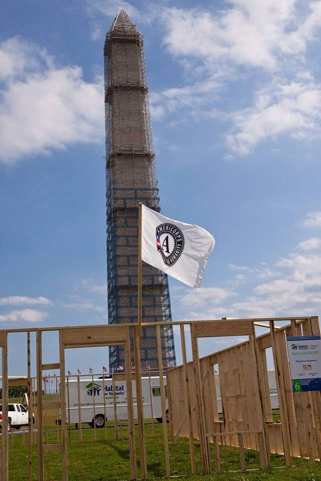 An AmeriCorps flag attached to the frame of a home under construction waves in front of the Washington Monument during the 2013 Veterans Build on the Mall in Washington, DC. (Corporation for National and Community Service Photo)