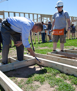 Rep. Randy Hultgren (IL) helps an AmeriCorps member as he hammers a nail into a frame of one of the homes during the 2013 Veterans Build on the Mall in Washington, DC. (Corporation for National and Community Service Photo)