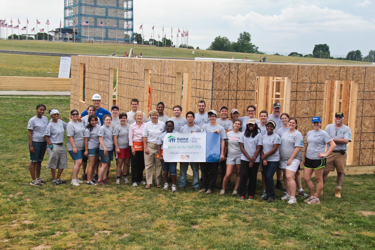 AmeriCorps members serving during the Veterans Build on the Mall pause for a photo in front of one of the frames under construction on the National Mall in Washington, DC on June 2, 2013. (Corporation for National and Community Service Photo)