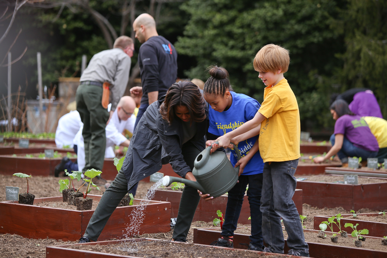 First Lady Michelle Obama helps students water the garden on the South Lawn for the White House Kitchen Garden. Corporation for National and Community Service Photo.