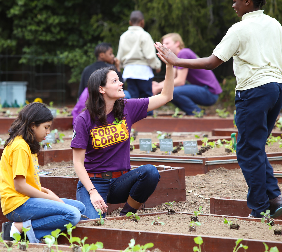 Food Corps member congratulates a student on a job well done at the White House Kitchen Garden. Corporation for National and Community Service Photo.