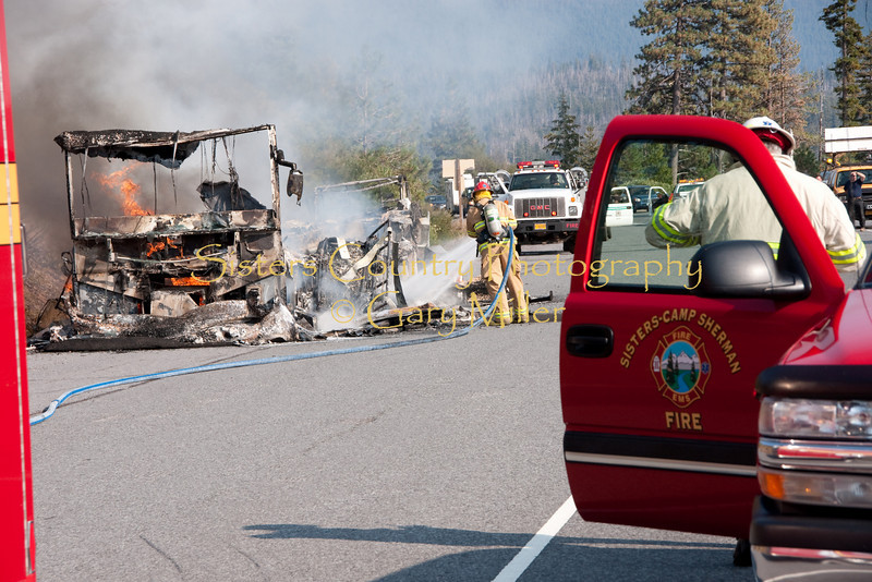 SCSFD Chief Tay Roberson gives an update to 911 Dispatch as Capt. Thornton Brown cools smoldering wreckage. A nearly new Class 'A' Motorhome towing a recreational vehicle burned to a melted skeleton of metal near the Mt. Washington viewpoint on the Highway 20's Santiam Pass near Sistere, OR on September 24th, 2009.