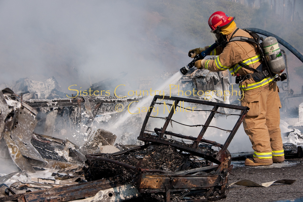 A nearly new Class 'A' Motorhome towing a recreational vehicle burned to a melted skeleton of metal near the Mt. Washington viewpoint on the Highway 20's Santiam Pass near Sistere, OR on September 24th, 2009. Sisters Fire Department Captain Thornton Brown hoses the hulk down with foam. Photo by Gary Miller