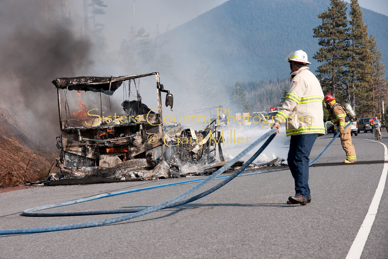 SCSFD Chief Tay Roberson pulls hose  as Capt. Thornton Brown cools smoldering wreckage. A nearly new Class 'A' Motorhome towing a recreational vehicle burned to a melted skeleton of metal near the Mt. Washington viewpoint on the Highway 20's Santiam Pass near Sistere, OR on September 24th, 2009.
