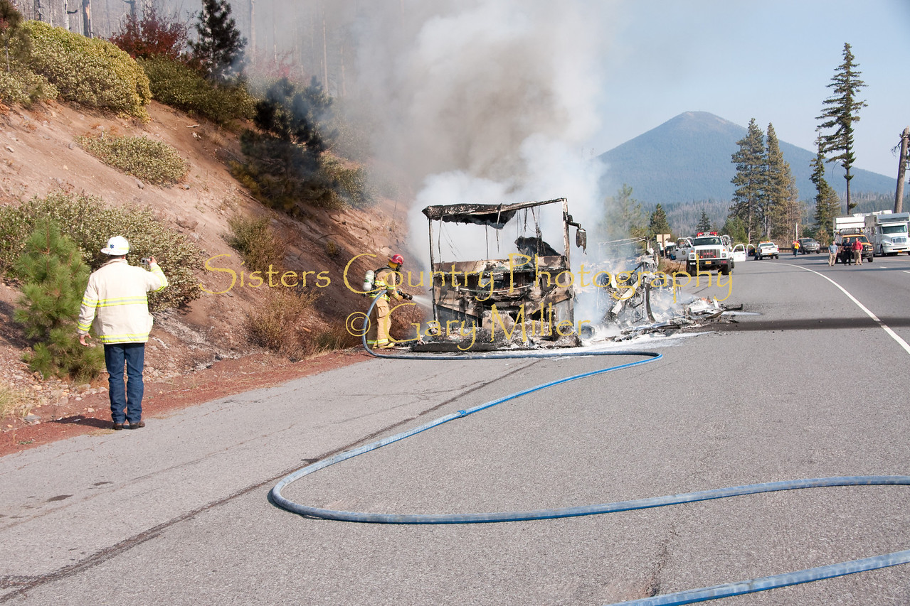 SCSFD Chief Tay Robertson fires off photos  as Capt. Thornton Brown cools smoldering wreckage. A nearly new Class 'A' Motorhome towing a recreational vehicle burned to a melted skeleton of metal near the Mt. Washington viewpoint on the Highway 20's Santiam Pass near Sistere, OR on September 24th, 2009.