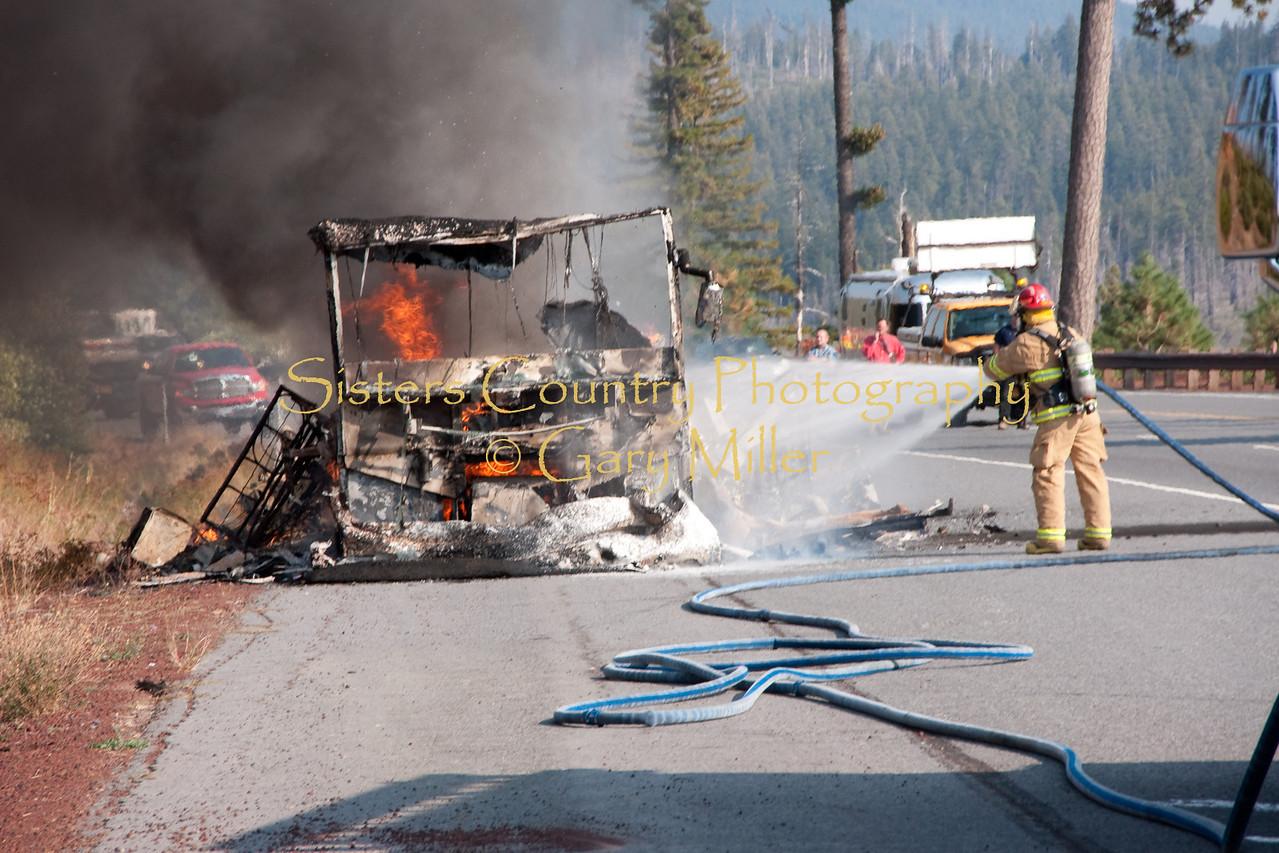 A nearly new Class 'A' Motorhome towing a recreational vehicle burned to a melted skeleton of metal near the Mt. Washington viewpoint on the Highway 20's Santiam Pass near Sistere, OR on September 24th, 2009. Here Sisters Fire Department Captain Thornton Brown sprays foam to cool the still hotly burning fire.
