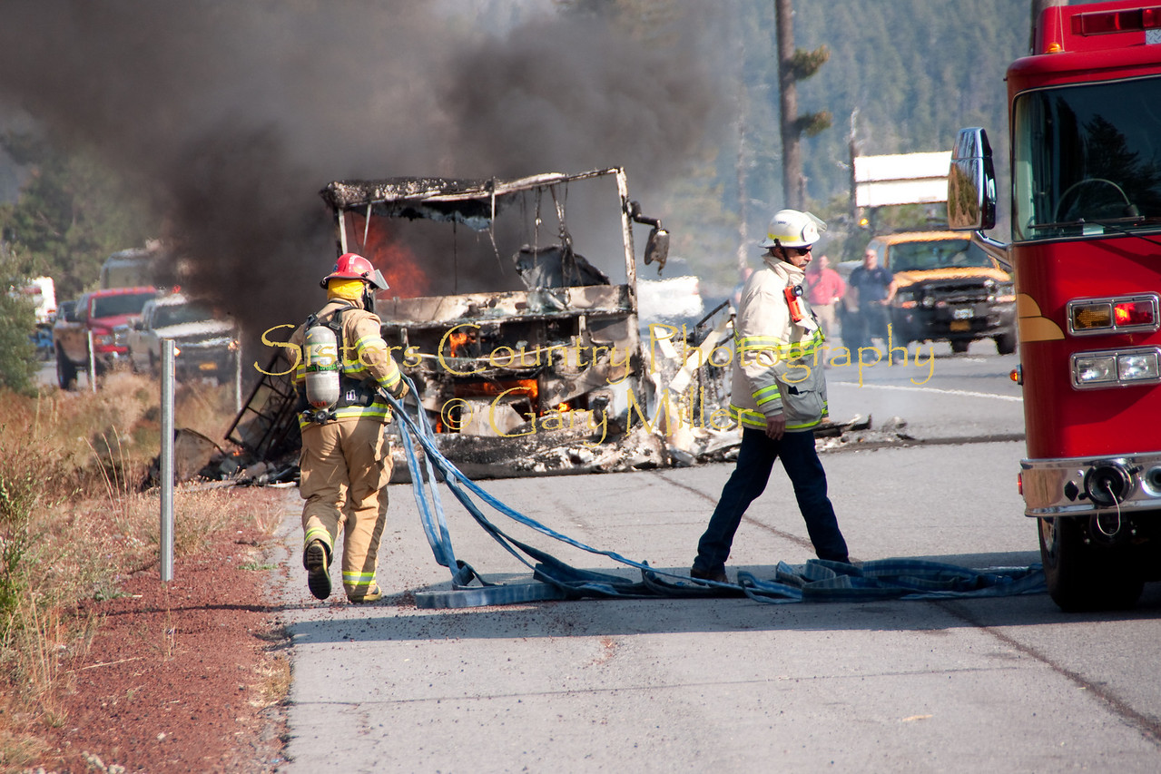 A nearly new Class 'A' Motorhome towing a recreational vehicle burned to a melted skeleton of metal near the Mt. Washington viewpoint on the Highway 20's Santiam Pass near Sistere, OR on September 24th, 2009. Sisters Fire Department Captain Thornton Brown and Fire Chief Tay Robertson pull initial attack hose off engine 721.