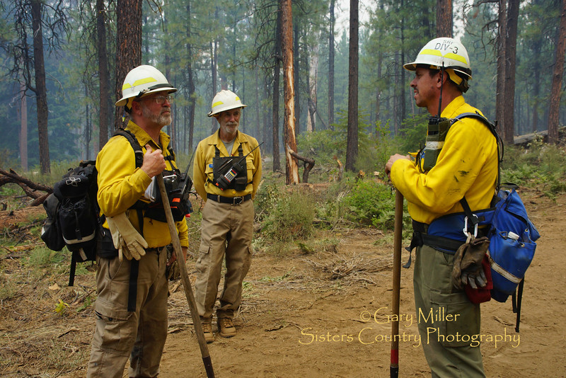 Division Supervisor Paul Johnson talks to other team members as fire crews work on back-fire burnout  operations July 9th. The Green Ridge Fire was a lightning caused wildfire located on the east wall Green Ridge in the Metolius Basin just north of Camp Sherman, Oregon near the Allingham Guard Station. The fire started on July 31, 2013 and was taken over by the NorCal Team 1 as part of the Cascade DIvision complex of lightning fires on August 3, 2013. Copyright © 2013 Gary N. Miller, Sisters Country Photography