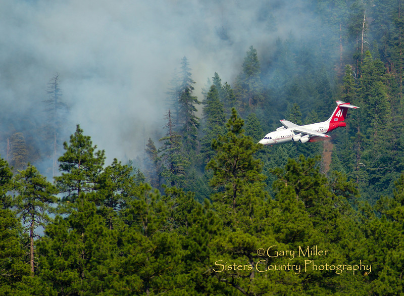 Air Tanker 41 makes an approach for a retardant drop tying in the bottom line of the Green Ridge Fire on August 5, 2013. The Green Ridge Fire was a lightning caused wildfire located on the east wall Green Ridge in the Metolius Basin just north of Camp Sherman, Oregon near the Allingham Guard Station. The fire started on July 31, 2013 and was taken over by the NorCal Team 1 as part of the Cascade DIvision complex of lightning fires on August 3, 2013. Copyright © 2013 Gary N. Miller, Sisters Country Photography